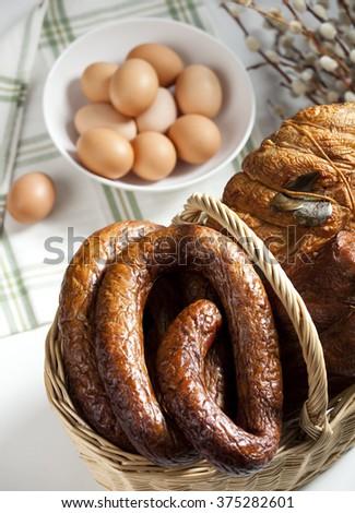 Easter basket filled with smoked cold meats. Eggs in white bowl - stock photo