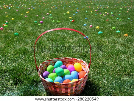 Easter basket in field with plastic eggs. - stock photo