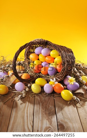 Easter Basket with easter eggs, narcissus and catkin on old weathered wooden board - stock photo