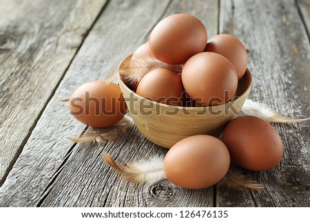 easter basket with easter eggs on wooden background - stock photo