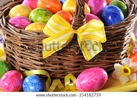 easter basket with many colored easter eggs and yellow bow - stock photo