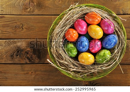 Easter basket with many colored hen�s eggs on old wooden board - stock photo