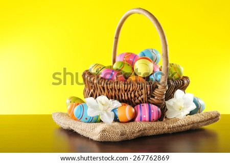 Easter basket with many painted easter eggs and narcissus