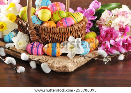 Easter basket with many painted easter eggs, narcissus and catkin - stock photo