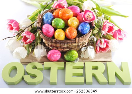 easter basket with tulips, easter eggs and easter writing - stock photo