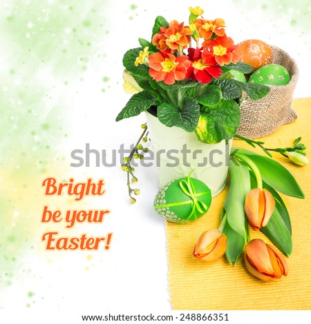 Easter border with orange tulips, primulas and spring decorations, space for your text - stock photo
