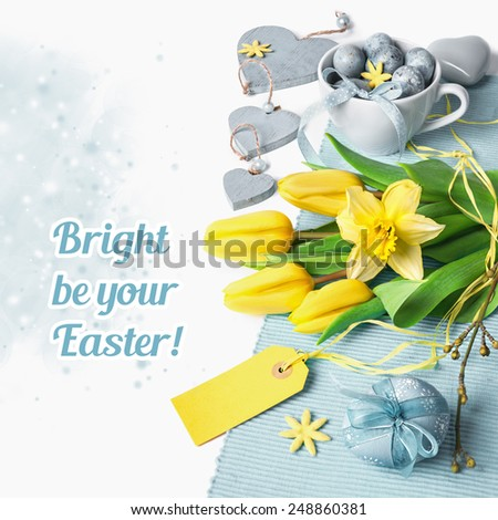 Easter border with yellow tulips and pale blue spring decorations, space for your text - stock photo