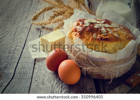 Easter bread and ingredients on rustic wood background, copy space, toned