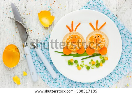 Easter breakfast for kids food art idea cute Easter chicks on branch morning snack on white background top view - stock photo