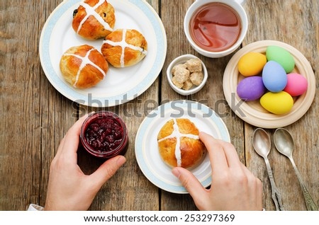 Easter Breakfast. Man holding the bun with a cross and a jar of jam. tinting. selective focus - stock photo
