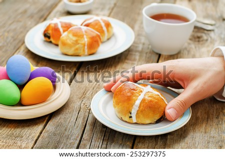Easter Breakfast. Man holding the bun with a cross. tinting. selective focus - stock photo