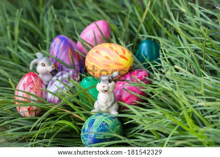 Easter bunnies and eggs on hiding in between the green grass close up