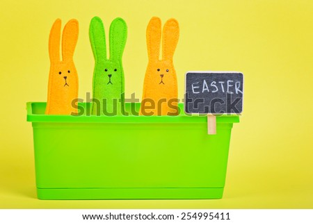 Easter Bunnies in flower pot with blackboard on yellow paper background - stock photo