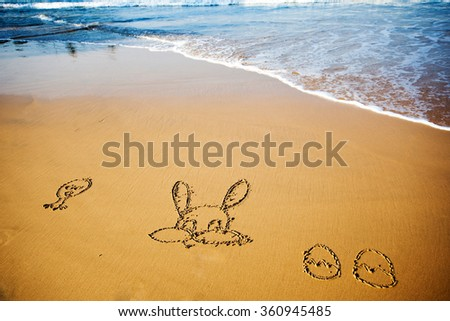 Easter bunny and eggs drawn in sand on tropical beach - stock photo
