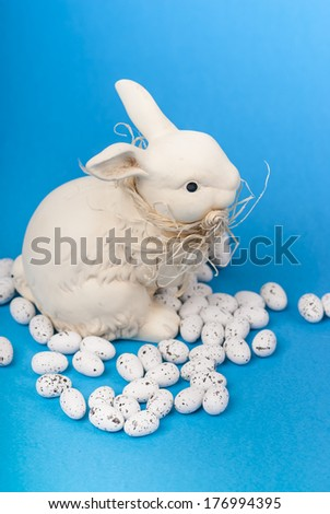 Easter bunny and eggs on blue close up. - stock photo