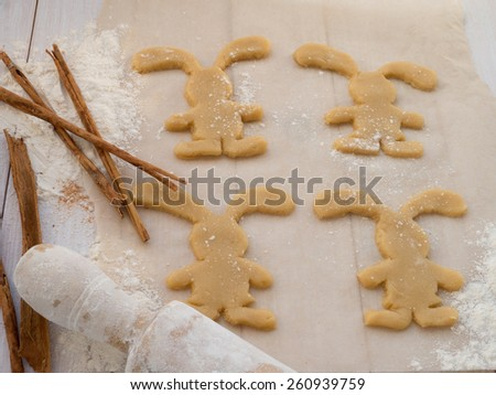 Easter Bunny cookies, cinnamon sticks and roller-pin - stock photo
