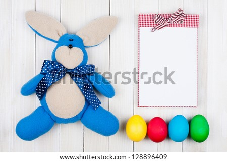 Easter bunny, eggs and notebook on white wood background