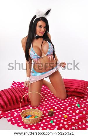 Easter bunny girl kneeling on picnic rug - stock photo
