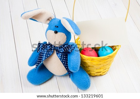 Easter bunny, , greeting card, eggs in basket on white wood background - stock photo