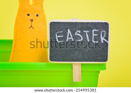 Easter Bunny in flower pot with blackboard on yellow paper background - stock photo