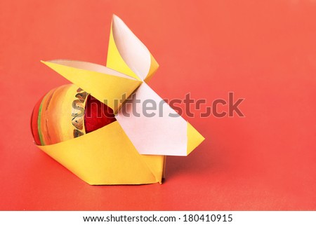 Easter bunny paper rabbit with painted egg on a orange background - stock photo