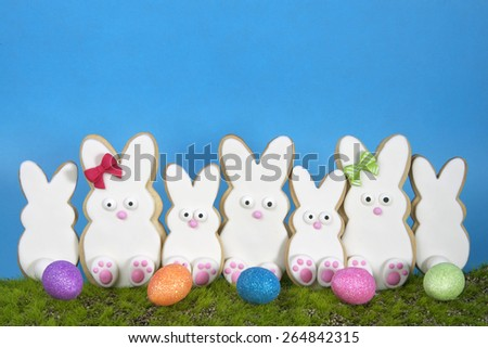 Easter Bunny Sugar Cookies homemade covered in home made marshmallow fondant, decorated with candy eyes, nose, feet and bow Large and small bunnies standing on pseudo grass blue background easter eggs - stock photo