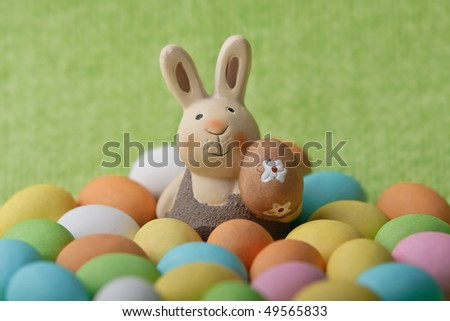 Easter bunny whit many colored easter eggs on a green background - stock photo