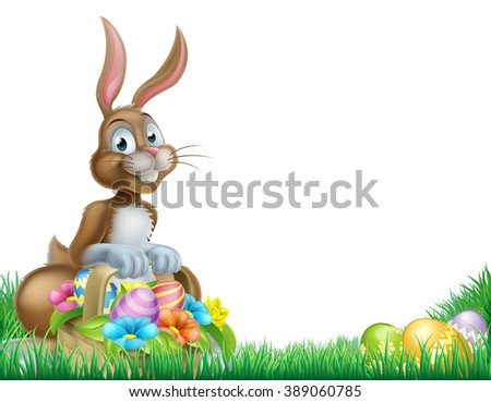 Easter bunny with a basket full of decorated chocolate Easter eggs in a field - stock photo