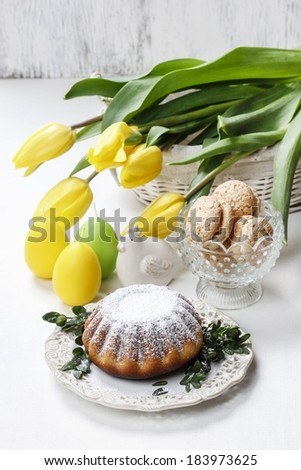 Easter cake and bouquet of yellow tulips on the table - stock photo