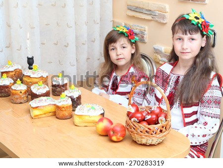 Easter cake and eggs. Girl in Ukrainian embroidery celebrates Easter