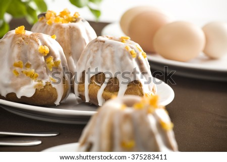 Easter cake on white plate. Two forks, more plates and cakes in background. All on brown table cloth. - stock photo
