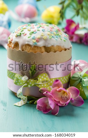 Easter cake, pink flowers and painted eggs on a turquoise table - stock photo
