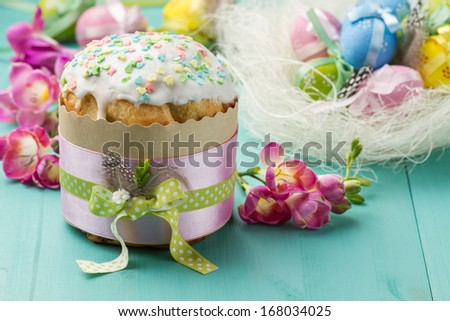 Easter cake, pink flowers and painted eggs on a turquoise table (horizontal shot) - stock photo