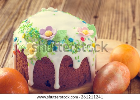 Easter cake with glace icing decoration and colored easter eggs on a rustic wooden table, soft pastel tones - stock photo