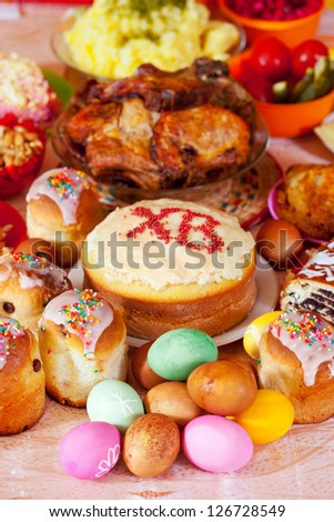 Easter cakes and other meal on festive table - stock photo