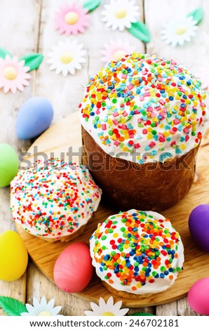Easter cakes with colorful topping on a white wood background. tinting. selective focus - stock photo