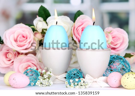 Easter candles with flowers on window background