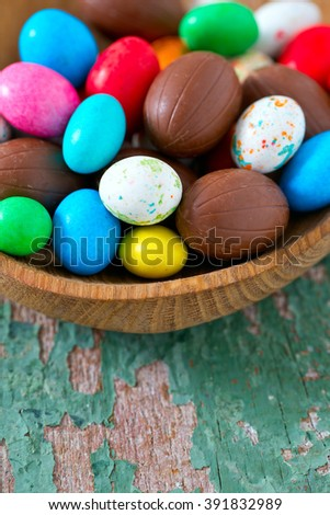 Easter candy eggs on old wooden surface - stock photo