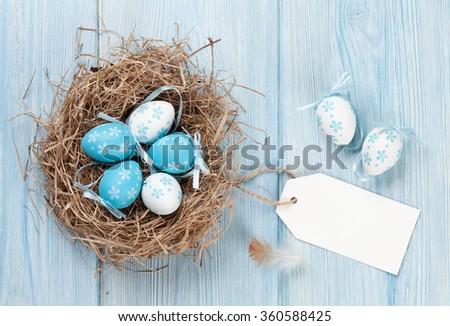 Easter card with eggs in nest on blue wooden table. Top view with copy space - stock photo