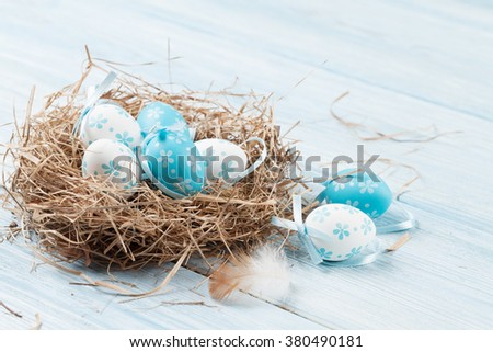 Easter card with eggs in nest over wood - stock photo