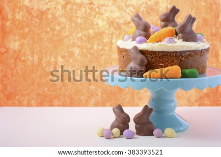 Easter Carrot Cake decorated with mini fondant carrots and chocolate bunnies on a white wood table with orange background, with copy space.  - stock photo
