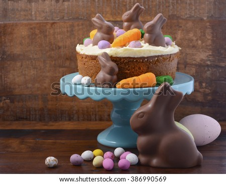 Easter Carrot Cake decorated with mini fondant carrots and chocolate bunnies on dark wood background, with copy space.   - stock photo