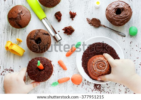 Easter carrot cakes cooking Kid hands decorated cupcakes chocolate sprinkles on a white table. Creative Easter baking, cooking process with a child in the kitchen - stock photo