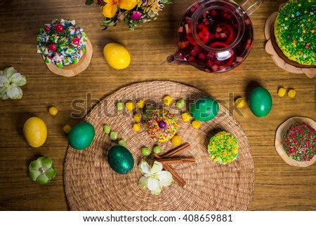Easter celebrating family dinner, multicolored eggs, flowers, sweet sprinkled cakes, cupcakes, fruit herbal tea,  sweets on wooden table, food holiday photo - stock photo