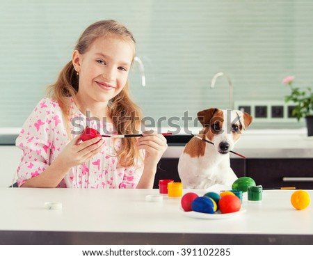 Easter. Child with dog painting eggs - stock photo