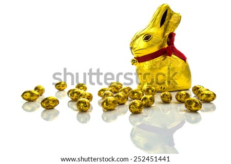 Easter chocolate bunny and golden eggs on white background - stock photo