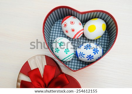 Easter colored eggs in a box in the shape of heart. - stock photo