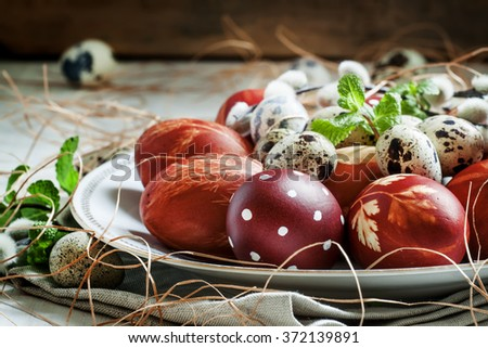 Easter colored eggs, quail eggs, twigs of willow on the white porcelain plate, selective focus - stock photo