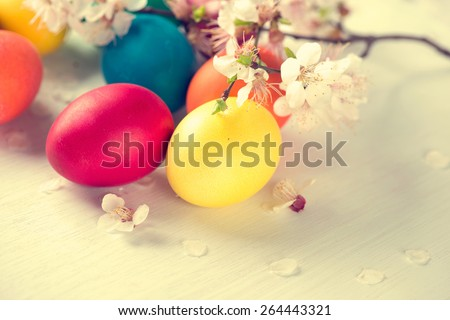 Easter. Colorful Easter eggs with spring blossom flowers over wooden background. Colored Egg Holiday border art design. Vintage toned - stock photo
