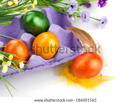 easter colorful eggs in violet tray,  bunch of flowers and feather on white background